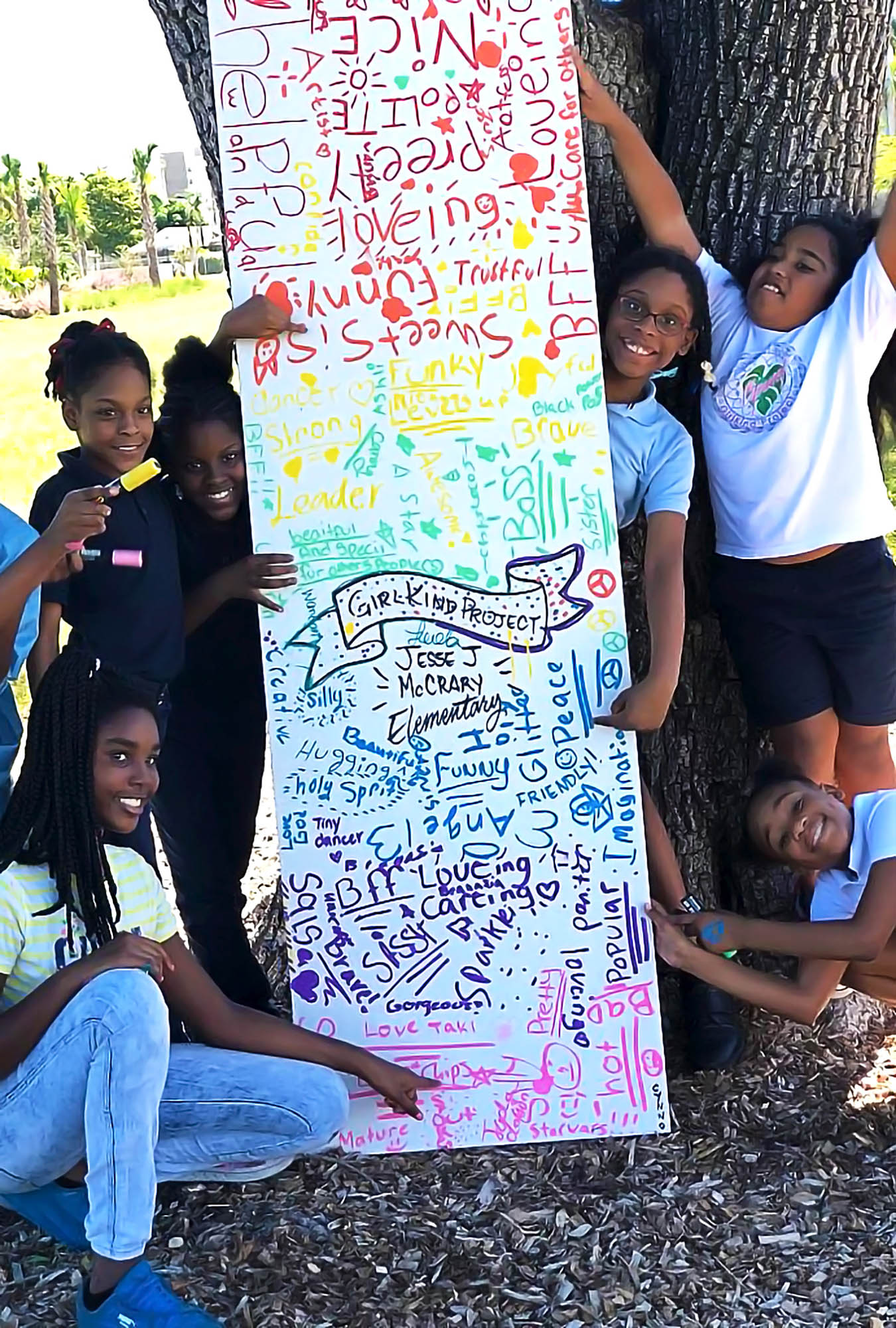 Students from Jesse J. McCrary, Jr Elementary School in Miami are posing with the GirlKind door to kindness they created